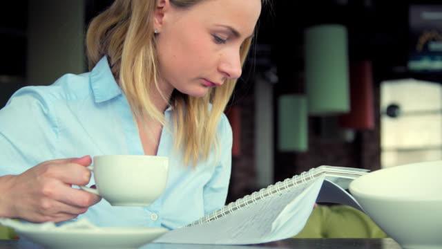 moderna flickan i en café dricka te, använder tabletten och skriver i anteckningsboken. vacker flicka i kaféet arbetar eller studerar. - bordsjordglob bildbanksvideor och videomaterial från bakom kulisserna