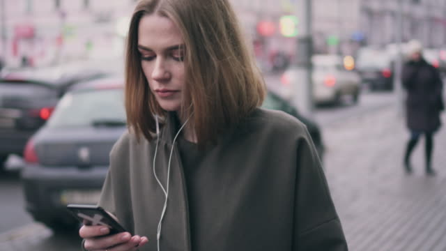 Modern girl using phone and headphones while walking on street video