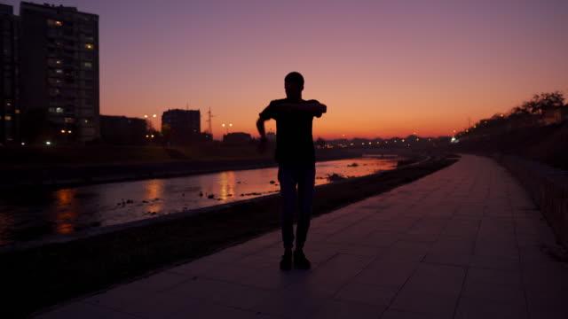 vidéos et rushes de danseur moderne de hip-hop exécutant dans le coucher du soleil - personnalité