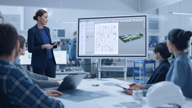 modern industrial factory meeting: confident female computer engineer uses digital interactive whiteboard, talks to a group of engineers, managers talks and shows 3d printed circuit board concept - chip komputerowy filmów i materiałów b-roll