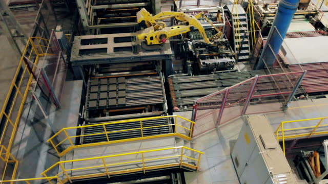 Modern industrial robotic arm works with bricks on a line.