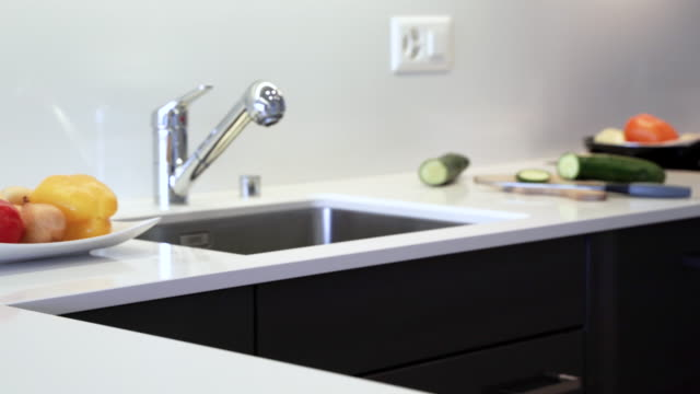 Modern kitchen countertop made of the marble slab. Kitchen cabinets are made of black flat panels.