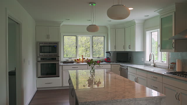 Modern kitchen interior in the luxury residential house, with wide windows and natural light. The camera moving forward and ending looking through the window onto the backyard.
