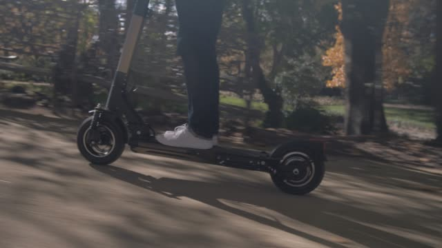 modern man using electric scooter in sunny park - monopattino elettrico video stock e b–roll