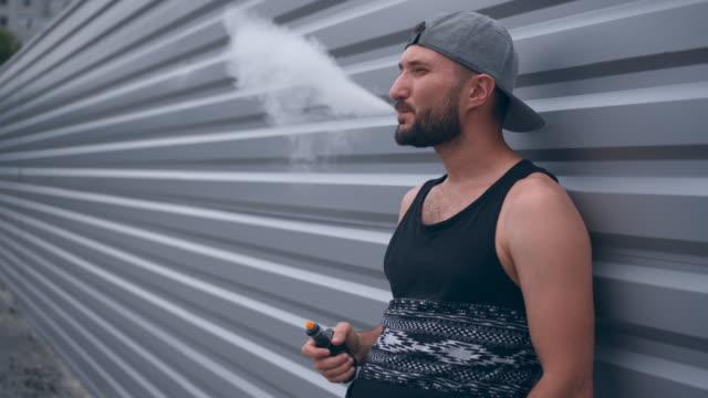 sakal sigara elektronik sigarette açık havada ile modern insan - nikotin stok videoları ve detay görüntü çekimi