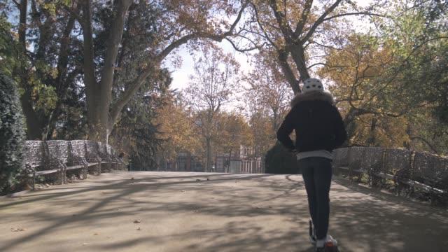modern man with helmet crossing a bridge on electric scooter - monopattino elettrico video stock e b–roll