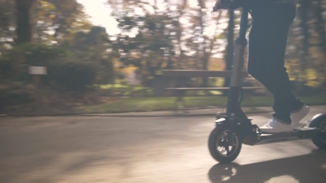 modern man with helmet using electric scooter in sunny park - monopattino elettrico video stock e b–roll