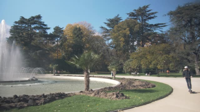 modern man with helmet using electric scooter in sunny park with fountain - monopattino elettrico video stock e b–roll