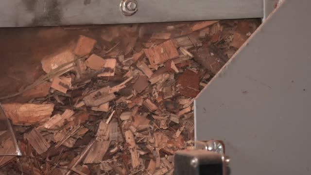 vídeos de stock e filmes b-roll de modern models of water heaters, working on wood waste. viewing window through which wood waste is visible. wood waste is loaded into the boiler. - madeira material