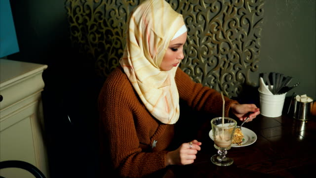 a modern muslim woman eats dessert and drinks a chocolate cocktail in a cafe - abbigliamento modesto video stock e b–roll