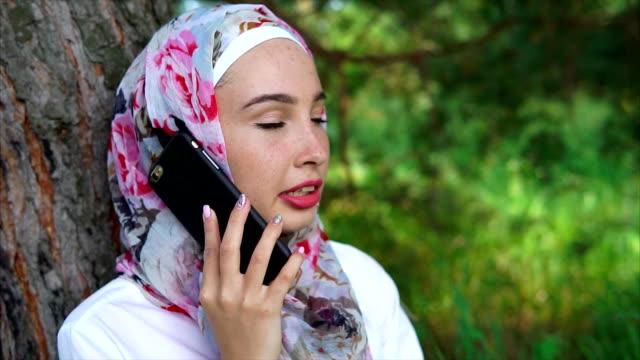 en modern muslimsk kvinna talar på en smartphone, hon sitter nära ett träd i parken - anständig klädsel bildbanksvideor och videomaterial från bakom kulisserna