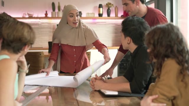 Modern Muslim woman wearing hijab lead the business meeting with multi-ethnic group of people. Unrolling the drawings. video
