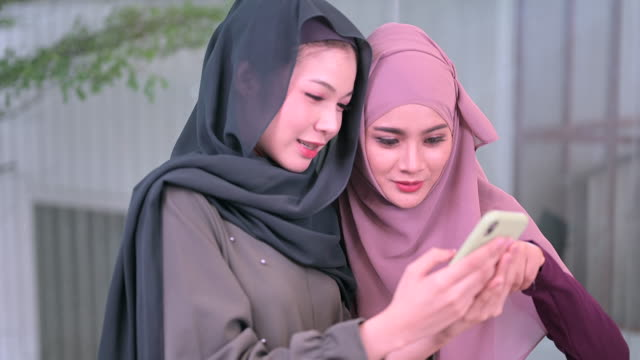 modern muslim women concept, using smart phone to take a picture and using for social network application - potere femminile video stock e b–roll