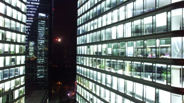 modern office buildings with glass wall in hangzhou at night 4k video