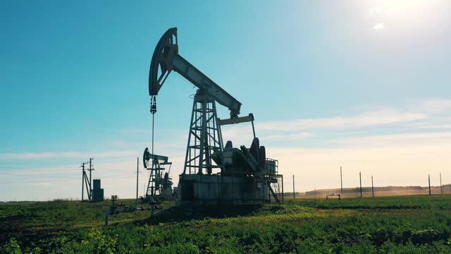 Modern oil pumpjack working in a filed in daylight video