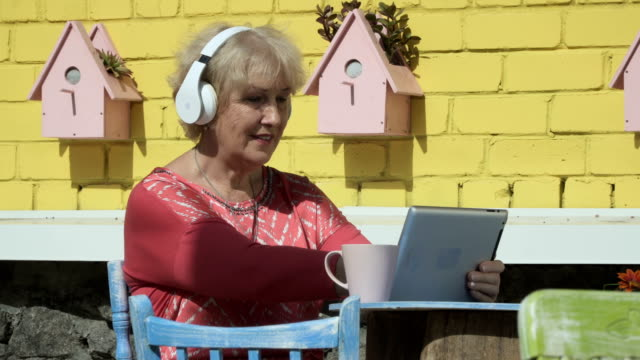 Modern old woman listen music in headphones and uses tablet video