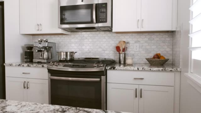 Modern Open Concept Home Interior The interior of a modern 'open concept' American residential home with the kitchen, dining area, and family room in a large open space. kitchen sink stock videos & royalty-free footage