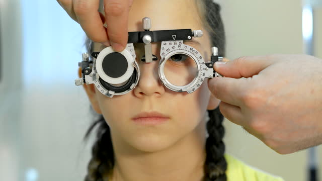 Modern ophthalmology clinic Close up of a teenager who checks the vision with the help of visionimetry. Ophthalmologist stands next to her, she checks the clarity of vision with the help of a visiometry ophthalmologist stock videos & royalty-free footage