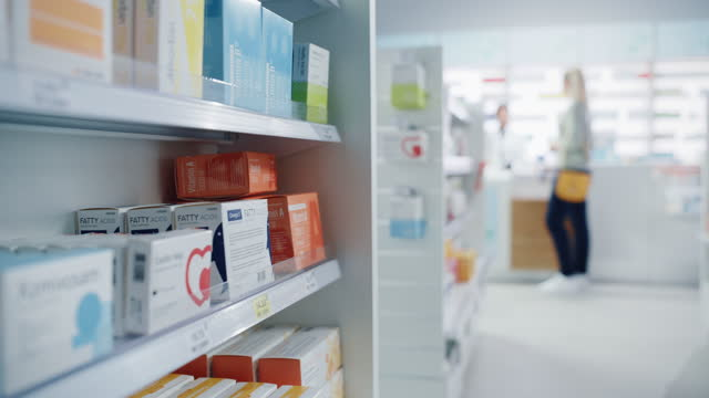 vídeos de stock e filmes b-roll de modern pharmacy drugstore with shelves full of packages full of modern medicine, drugs, vitamin boxes, supplements. in background anonymous customer buys products from pharmacist standing at counter - desfocado focagem