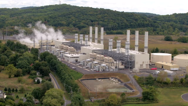 aerial: modern power station facility using natural gas to produce electricity - centrale elettrica video stock e b–roll
