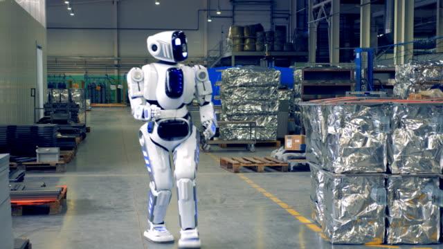 現代ロボットは、生産現場でカメラに笑顔について説明します。 - ロボット点の映像素材/bロール