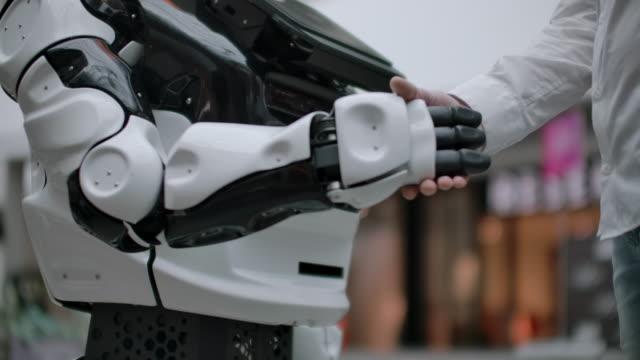 vídeos de stock e filmes b-roll de modern robotic technologies. a man communicates with a robot, presses a plastic mechanical arm to the robot, handshake - padrão repetido