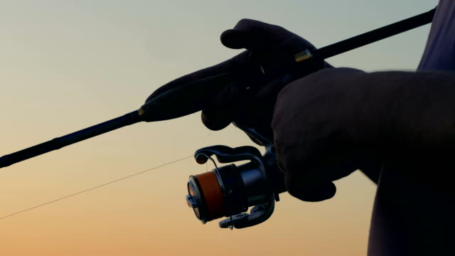Modern rod with a spinning equipment, close up. A fisherman catches fish with a spinning rod. catching stock videos & royalty-free footage