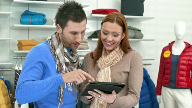 HD DOLLY: Modern Saleswoman Assisting Customer HD1080p: DOLLY shot of a saleswoman using a digital tablet while assisting young man choosing the right clothes in a boutique. saleswoman stock videos & royalty-free footage