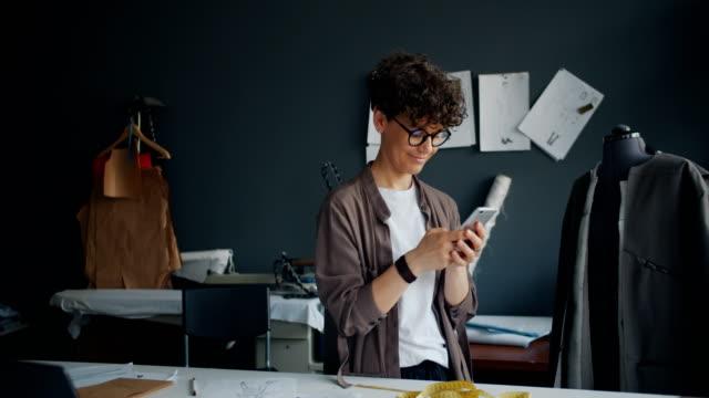 modern sömmerska med hjälp av smartphone på jobbet beröring skärm textning leende - entreprenör bildbanksvideor och videomaterial från bakom kulisserna