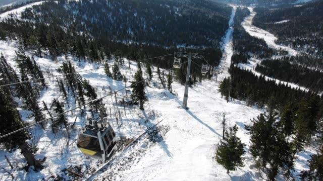 modern ski lift cabins move over extreme tracks on hill - vídeo