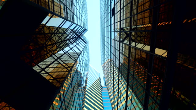 modern skyscrapers in business district against blue sky - acciaio video stock e b–roll