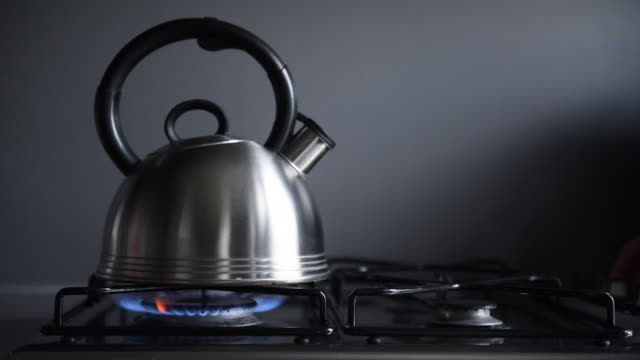 modern stainless kettle put to boil water on gas cooker. blue fire is being lit up. human hand in the shot. - metallizzato video stock e b–roll