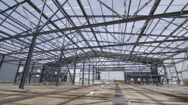 Modern storehouse construction site, structural steel structure of new commercial building against. Construction of modern factory or warehouse. video