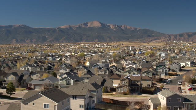 AERIAL: Modern suburban village at the foothills of Rocky Mountains on sunny day