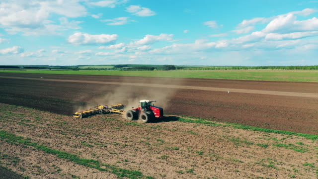 Modern tractor works on a land, sowing. Modern tractor works on a land, sowing. 4K agricultural occupation stock videos & royalty-free footage