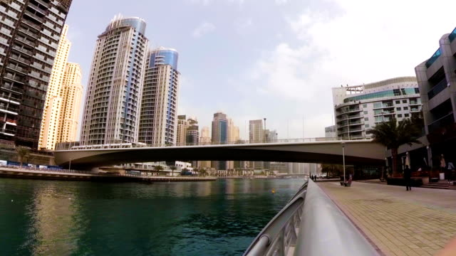 Modern tram passing over the bridge across the river among skyscrapers in Dubai Marina, UAE video