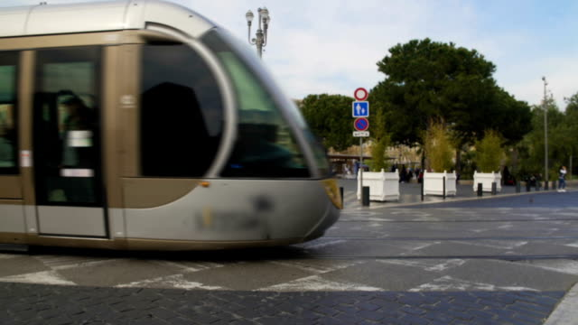 Modern tram with passengers moving in city center, public transportation