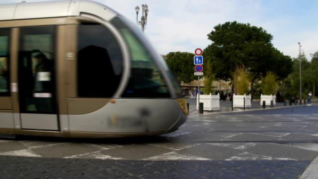 tram moderno con passeggeri che si muovono nel centro della città, mezzi pubblici - tranvia video stock e b–roll