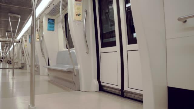 vidéos et rushes de train de métro de couleur blanche moderne attendant à la gare, puis fermant deux paires de portes et de parcimonie. métro express conduisant rapidement sous terre. transport public au tunnel illuminé de l'une des plus anciennes villes d'italie - rome - wagon
