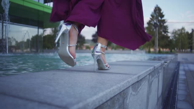 Modern woman walking in silver high heels on a part of fountain
