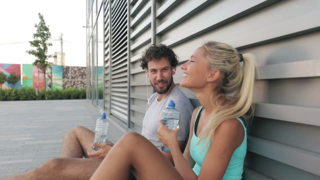 Modern young man and woman making pause after jogging / exercise in urban area.