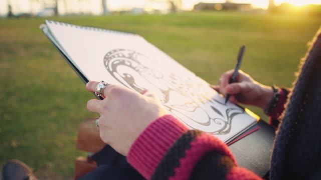 modern young stylish male paint artist drawing sketches in park - pittore video stock e b–roll