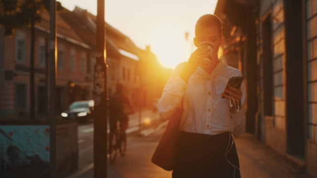 MS Modern young woman walking in the city at sunset, take away coffee