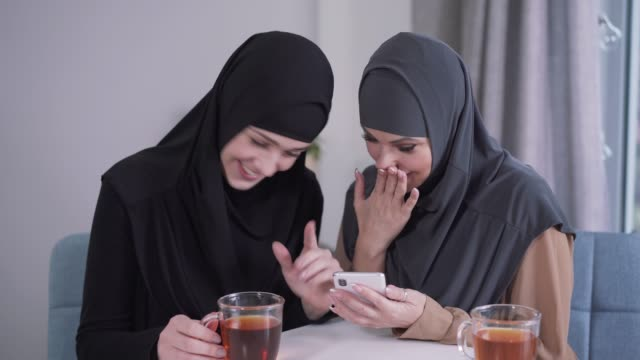 modern-looking muslim woman showing smartphone screen to modest friend in hijab. two women reacting emotionally at social media. modern technologies, communication, lifestyle. - abbigliamento modesto video stock e b–roll