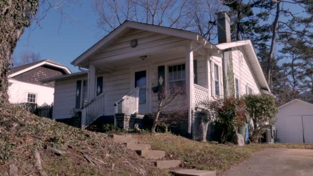 vídeos de stock e filmes b-roll de modest arts and crafts bungalow single family home establishing shot - driveway, no people