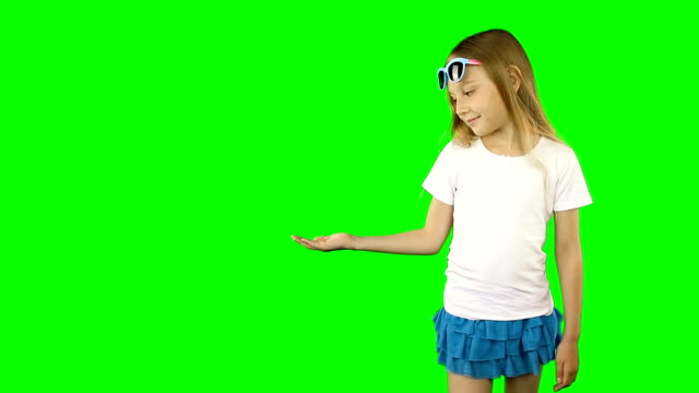 vídeos de stock e filmes b-roll de modest little girl laughs and holds a hand with an empty palm. template for advertising. can put something on the girl's hand. clip contains solid green instead alpha channel. - teeshirt template