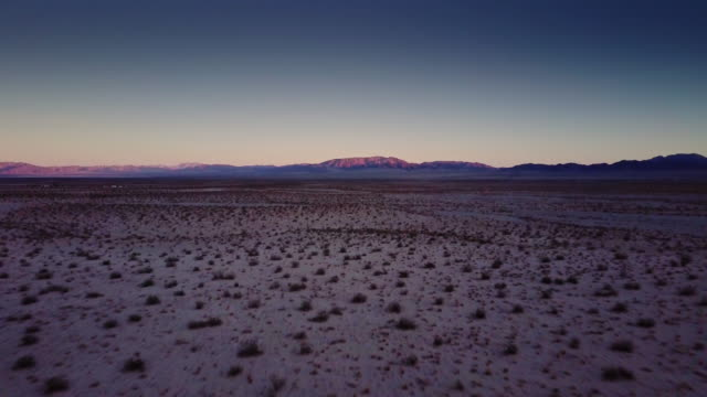 Mojave Desert at Twilight - Drone Shot Drone flight over open desert near Twentynine Palms, California, with the rays of the sun still touching the hills. mojave desert stock videos & royalty-free footage