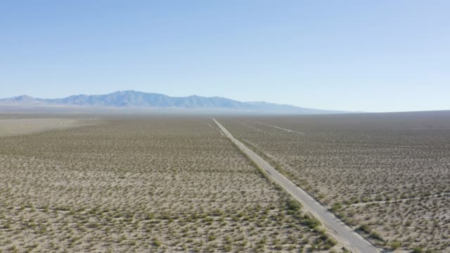 Mojave desert road Long straight lonely road in the middle of the Mojave desert mojave desert stock videos & royalty-free footage