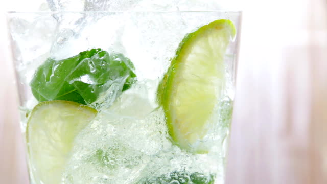Mojito cocktail drink is poured into a glass - vídeo