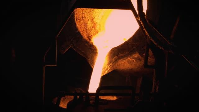 fusione dei metalli fusi, l'operatore lavora sodo a maschiare il metallo fuso dal forno alla siviera per versarlo in una fabbrica di fonderia - attrezzatura energetica video stock e b–roll